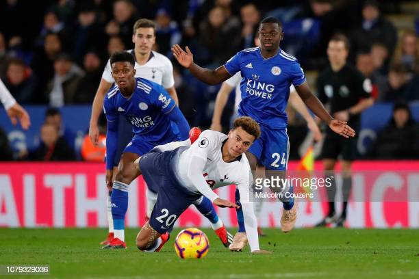 Dele Alli of Tottenham Hotspur falls under a challenge from Nampalys Mendy of Leicester City during the Premier League match between Leicester City...