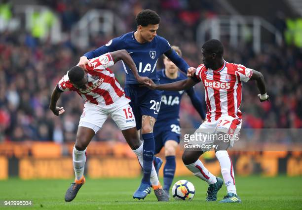 Dele Alli of Tottenham Hotspur is challenged by Bruno Martins Indi of Stoke City and Badou Ndiaye of Stoke City during the Premier League match...