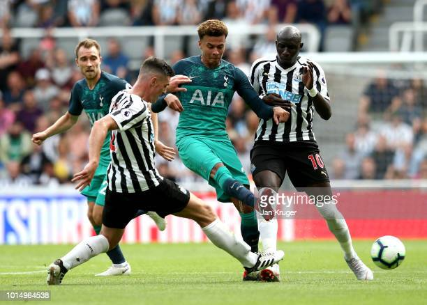 Dele Alli of Tottenham Hotspur is challenged by Ciaran Clark of Newcastle United and Mohamed Diame of Newcastle United during the Premier League...