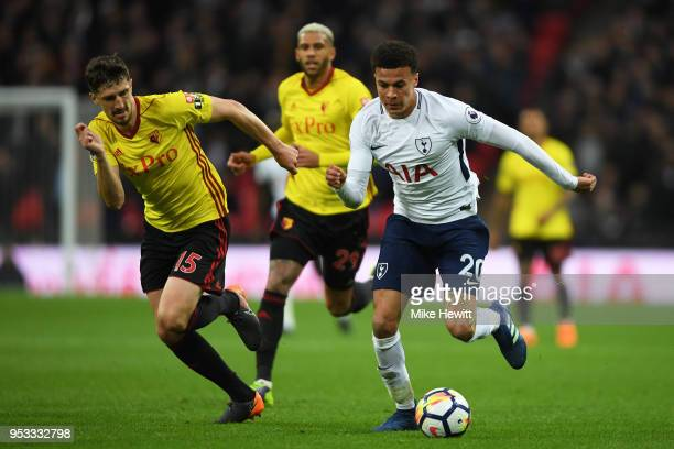 Dele Alli of Tottenham Hotspur is challenged by Craig Cathcart of Watford during the Premier League match between Tottenham Hotspur and Watford at...