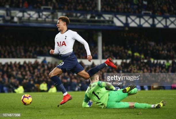 Dele Alli of Tottenham Hotspur is challenged by Jordan Pickford of Everton during the Premier League match between Everton FC and Tottenham Hotspur...