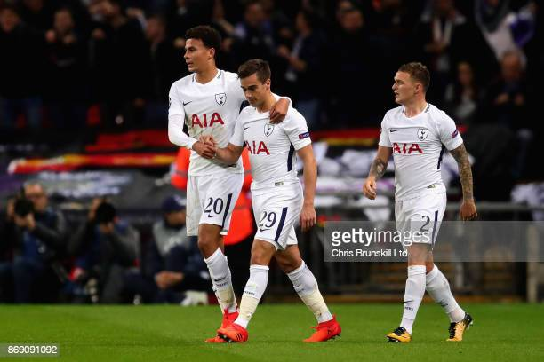 Dele Alli of Tottenham Hotspur is congratulated by teammate Harry Winks after scoring the opening goal during the UEFA Champions League group H match...