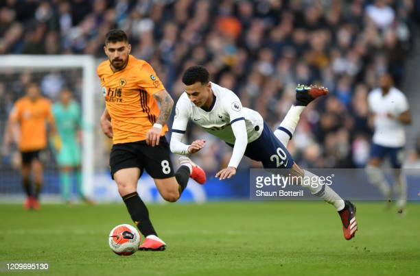 Dele Alli of Tottenham Hotspur is fouled by Willy Boly of Wolverhampton Wanderers as Ruben Neves looks on during the Premier League match between...