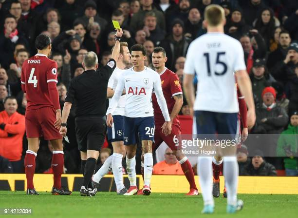 Dele Alli of Tottenham Hotspur is shown a yellow card by referee Jonathan Moss for diving during the Premier League match between Liverpool and...