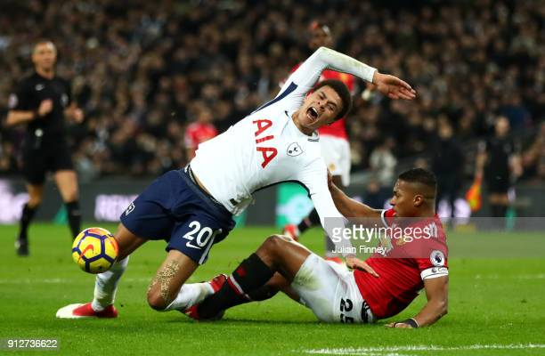 Dele Alli of Tottenham Hotspur is tackled by Antonio Valencia of Manchester United during the Premier League match between Tottenham Hotspur and...