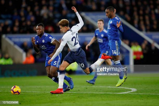 Dele Alli of Tottenham Hotspur runs past Wes Morgan and Ricardo Pereira of Leicester City during the Premier League match between Leicester City and...