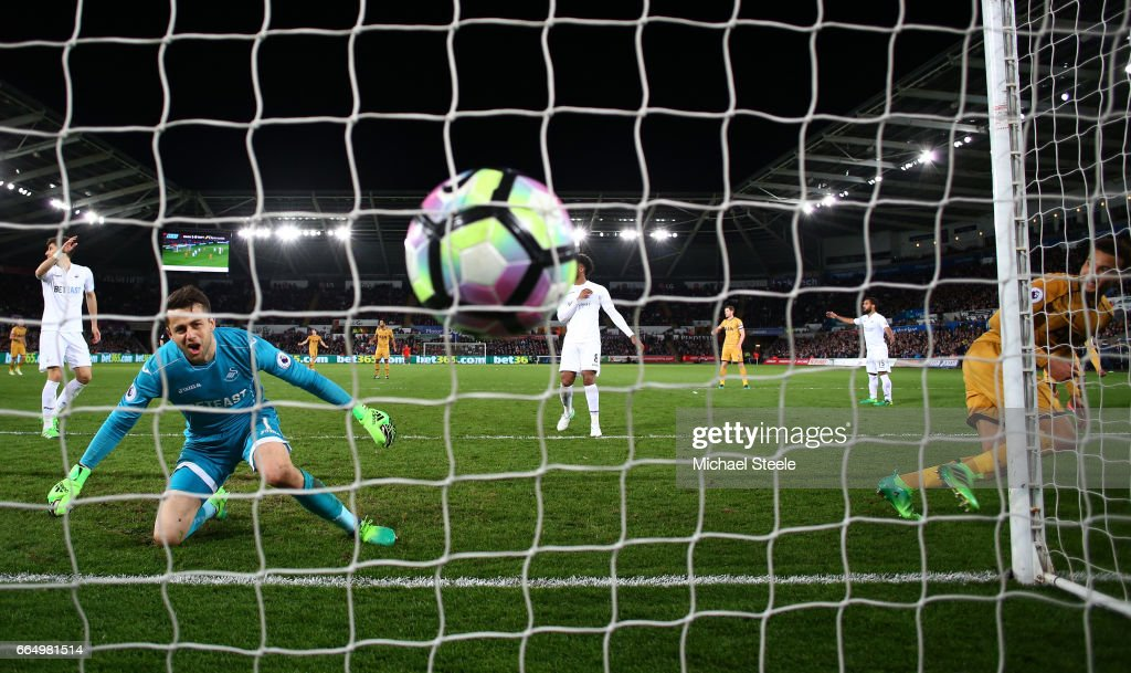 Dele Alli of Tottenham Hotspur (R) scores his sides first goal during the Premier League match between Swansea City and Tottenham Hotspur at the Liberty Stadium on April 5, 2017 in Swansea, Wales.
