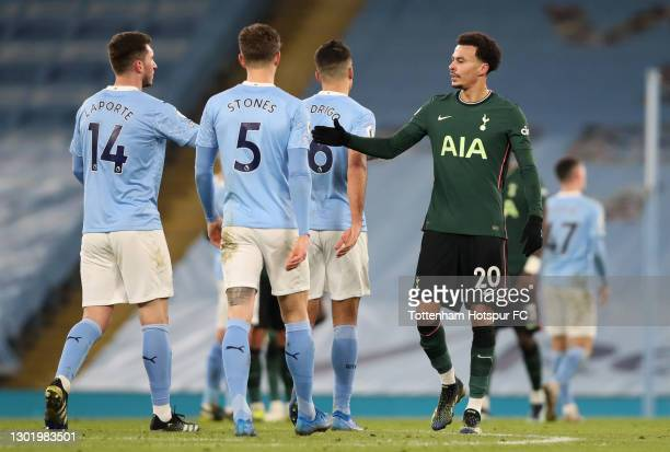 Dele Alli of Tottenham Hotspur shakes hands with Aymeric Laporte and John Stones of Manchester City following the Premier League match between...