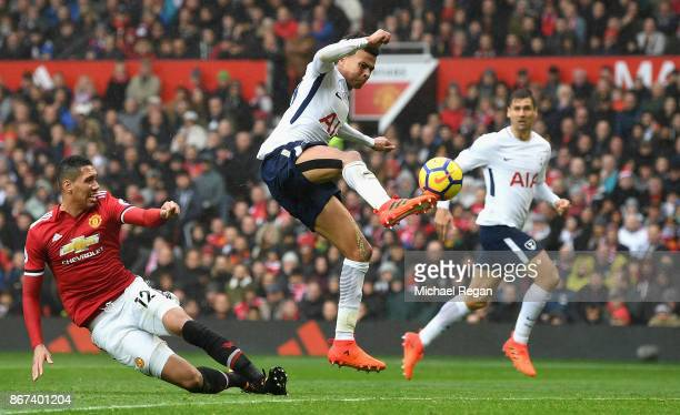 Dele Alli of Tottenham Hotspur shoots as Chris Smalling of Manchester United attempts to tackle during the Premier League match between Manchester...