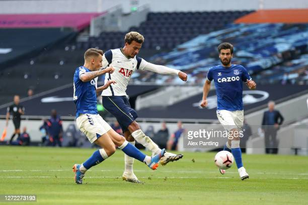 Dele Alli of Tottenham Hotspur shoots as he is challenged by Lucas Digne of Everton during the Premier League match between Tottenham Hotspur and...