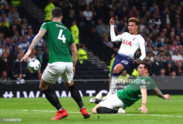 Dele Alli of Tottenham Hotspur shoots past Lewis Dunk and Shane Duffy of Brighton and Hove Albion during the Premier League match between Tottenham...
