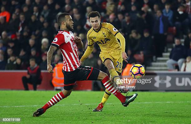 Dele Alli of Tottenham Hotspur shoots past Ryan Bertrand of Southampton as he scores theor fourth goal during the Premier League match between...