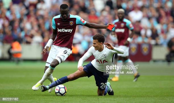 Dele Alli of Tottenham Hotspur tackles Cheikhou Kouyate of West Ham United who is carrying a red card during the Premier League match between West...