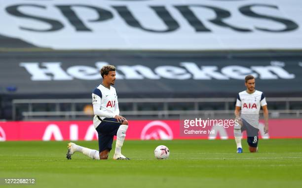 Dele Alli of Tottenham Hotspur takes a knee in support of the Black Lives Matter movement prior to the Premier League match between Tottenham Hotspur...