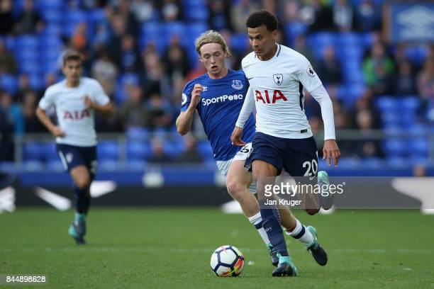 Dele Alli of Tottenham Hotspur takes the ball past Tom Davies of Everton during the Premier League match between Everton and Tottenham Hotspur at...