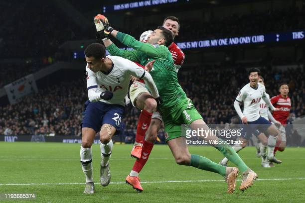 Dele Alli of Tottenham, Jonny Howson of Middlesbrough and goalkeeper Tomas Mejias go for the ball during the FA Cup Third Round Replay match between...