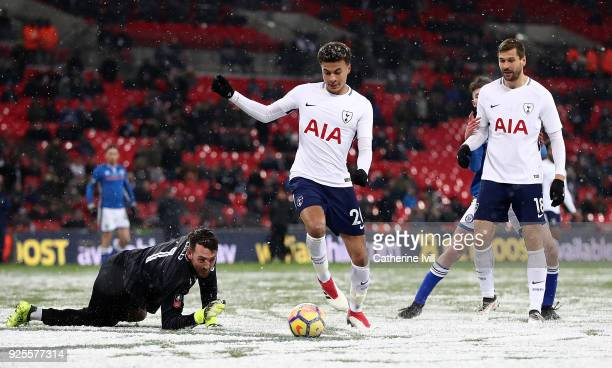 Dele Alli of Tottenham takes the ball round Josh Lillis of Rochdale during The Emirates FA Cup Fifth Round Replay match between Tottenham Hotspur and...