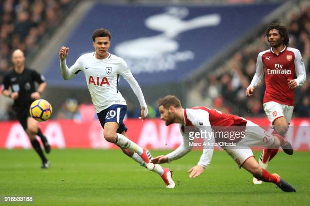 Dele Alli of Tottenham watches as Shkodran Mustafi of Arsenal heads the ball clear during the Premier League match between Tottenham Hotspur and...