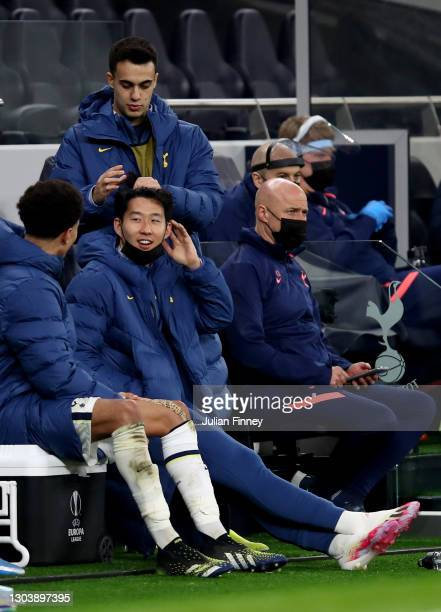 Dele Alli, Son Heung-Min and Sergio Reguilon of Tottenham Hotspur interact on the substitutes bench during the UEFA Europa League Round of 32 match...