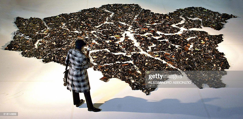 A delegate at the Metropolitan Police Gun Crime Conference in London admires Lucy Wood's artwork entitled 'Map 272183', 02 December, 2004. The artwork measures 8 by 6.26 metres and is made up of a sizeable portion of the three thousand and eighty five weapons that were handed in under the Gun Amnesty of 2003. .