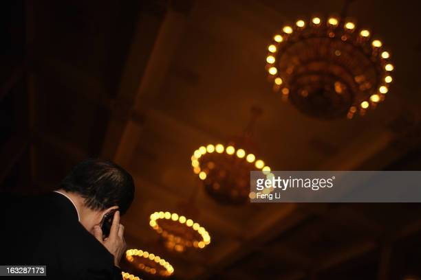 A delegate calls with iPhone as attending a plenary session of the Chinese People's Political Consultative Conference at Beijing's Great Hall of the...