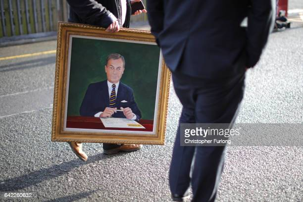 A delegate carries a painting of Nigel Farage MEP as UKIP party members arrive for the UKIP annual conference at the Macron Stadium on February 17...