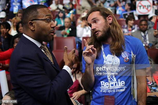 Delegate Chris Davis of Centennial CO and supporter of Bernie Sanders speaks with Sen Wesley Bishop of New Orleans and Hillary Clinton supporter on...
