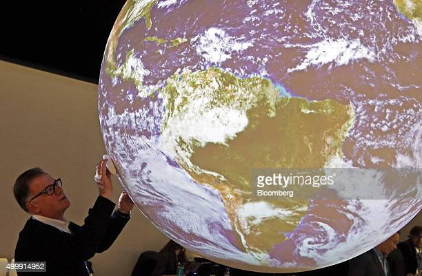 A delegate cleans an illuminated globe as it hangs in the US pavillion at the United Nations COP21 climate summit at Le Bourget in Paris France on...