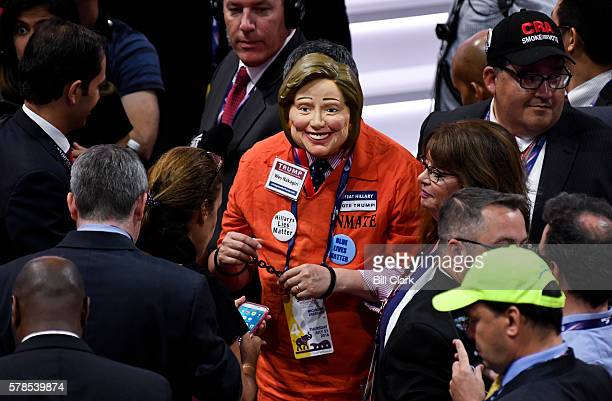 A delegate deseed as Hillary Clinton in a prison jumpsuit walks the floor of the Quicken Loans Arena at the 2016 Republican National Convention in...