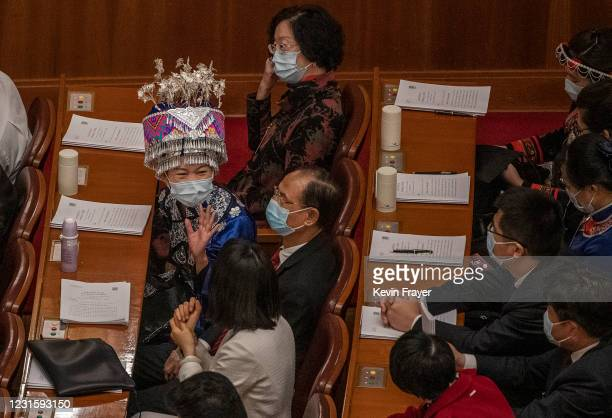 Delegate dressed in traditional costume of the Miao people talks to another delegate before the second plenary session of the National People's...