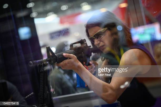Delegate fires a gun on the Ultimate Training Munitions testing area on day one of the DSEI exhibition at ExCel on September 14, 2021 in London,...