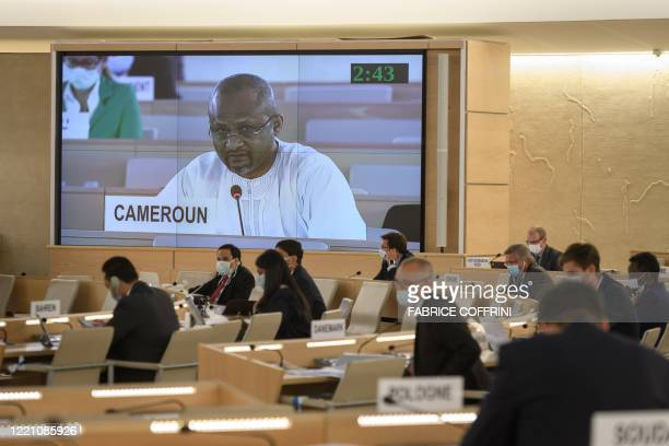 A delegate from Cameroon is seen delivering a speech on a giant screen during the vote of a watered down resolution condemning structural racism and...