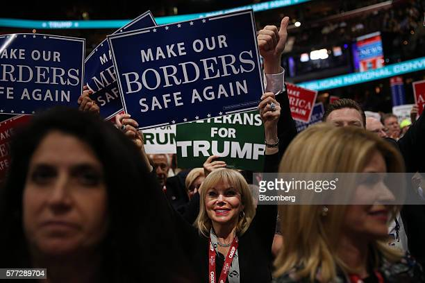 A delegate holds a sign reading Make Our Borders Safe Again during the Republican National Convention in Cleveland Ohio US on Monday July 18 2016...