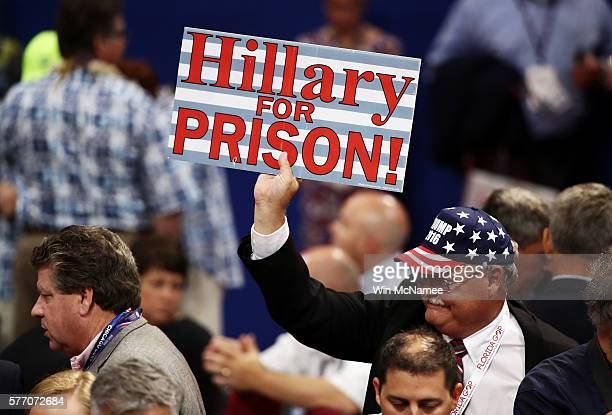 A delegate holds a sign that reads Hillary For Prison on the floor before the start of the first day of the Republican National Convention on July 18...