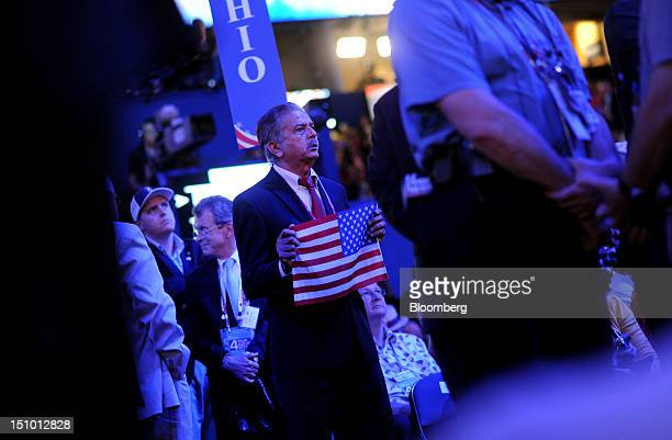 A delegate holds a US flag while listening at the Republican National Convention in Tampa Florida US on Thursday Aug 30 2012 Republican presidential...