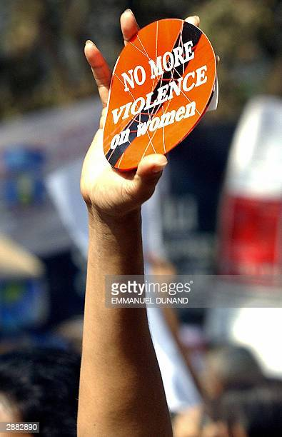 A delegate holds aloft stickers during a protest against violence against women after a delegate to the 2004 World Social Forum was accused of raping...