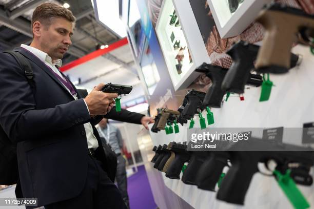 A delegate inspects one of the pistols displayed on the Beretta Defense Technologies stand on day one of the DSEI arms fair at ExCel on September 10...