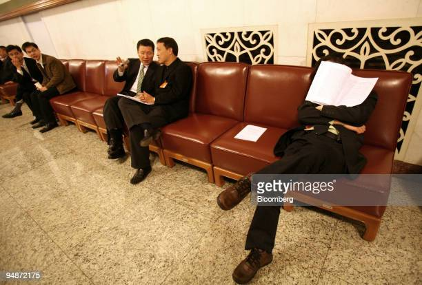 Delegate naps with a copy of a speech by Wen Jiabao, China's premier, over his face in the Great Hall of the People during the opening session of...