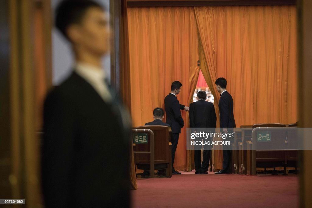 TOPSHOT - A delegate (2nd R) passes through curtains inside the Great Hall of the People during the opening session of the National People's Congress, China's legislature, in Beijing on March 5, 2018. Thousands of Chinese legislators erupted into enthusiastic applause over plans to give President Xi Jinping a lifetime mandate to mould the Asian giant into a global superpower. /
