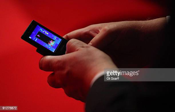 A delegate plays a game of tetris on his mobile phone during the speeches on the fourth day of the Labour Party Conference on September 30 2009 in...