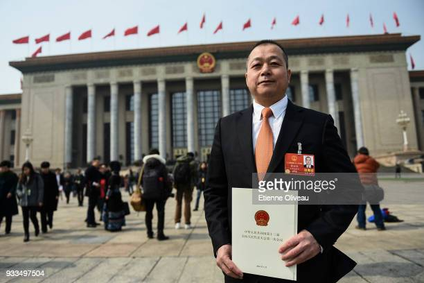 A delegate poses with the envelope that contained his ballot after the sixth plenary session of the National People's Congress at the Great Hall of...