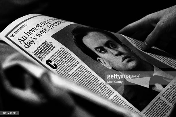 A delegate reads a newspaper article about Ed Miliband as they listen to speakers in the conference hall at the Labour Party conference on September...