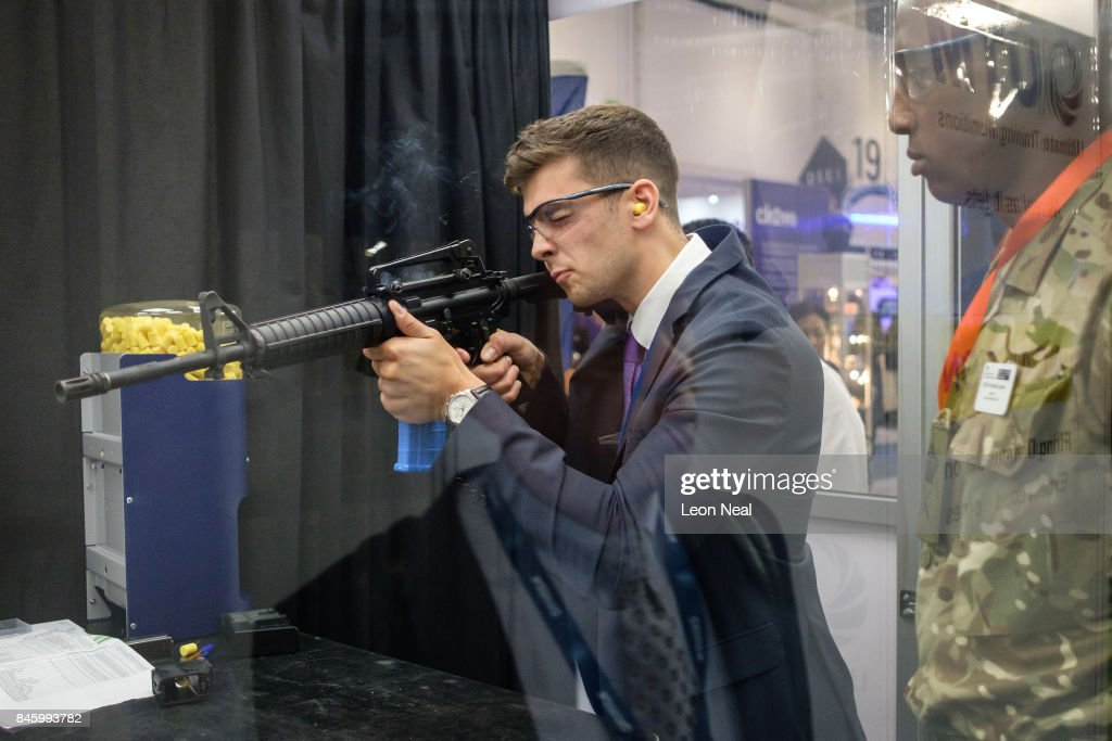 A delegate shoots at a target with non-lethal rounds on the 'Ultimate Training Munitions' display stand at the DSEI event at the ExCel centre on September 12, 2017 in London, England. The annual weapons and security trade fair sees manufacturers of all aspects of military, naval, airforce and security from all over the world display their latest designs to delegates.