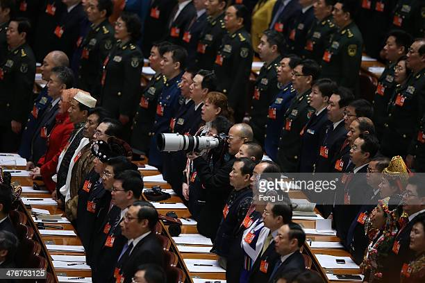 Delegate shoots pictures as other delegates sing the national anthem at the beginning of the opening session of the National People's Congress at the...