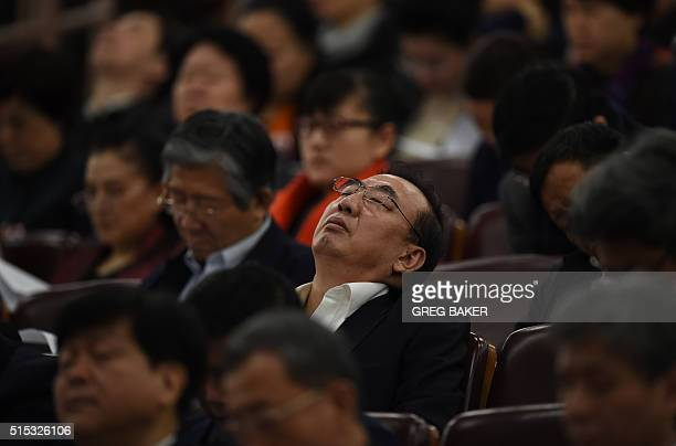A delegate sleeps through speeches during the third plenary session of the National People's Congress at the Great Hall of the People in Beijing on...