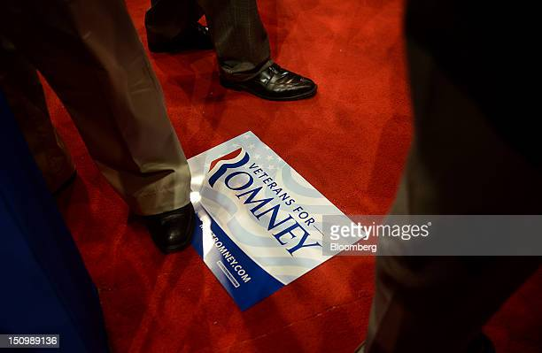 """Delegate stands on a """"Veterans for Romney"""" sign at the Republican National Convention in Tampa, Florida, U.S., on Wednesday, Aug. 29, 2012...."""