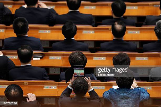 Delegate uses an Apple Mini to take a picture during the fifth plenary meeting of the National People's Congress at the Great Hall of the People on...