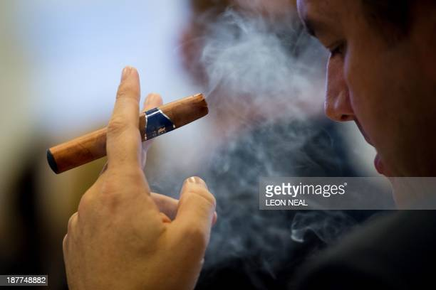 A delegate uses an ecigar during 'The ECigarette Summit' at the Royal Academy in central London on November 12 2013 The merits of ecigarettes were...