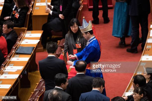 A delegate vote during the fifth plenary session of the first session of the 13th National People's Congress at the Great Hall of the People in...