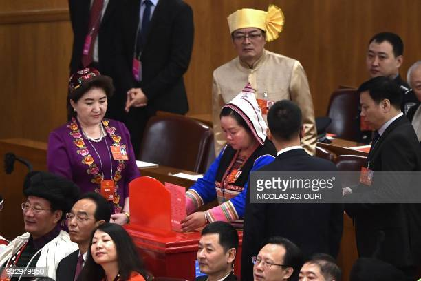 A delegate votes during the fifth plenary session of the first session of the 13th National People's Congress at the Great Hall of the People in...